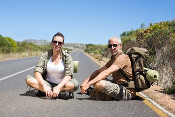 Hitch hiking couple sitting on the road