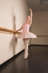 Beautiful ballerina standing en pointe holding barre