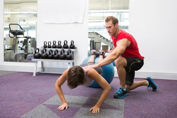 Personal trainer with client doing push up on exercise ball