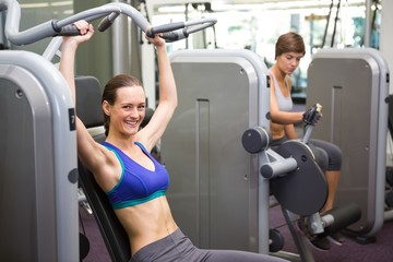 Healthy brunette using weights machine for arms