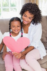Pretty mother sitting on couch with daughter reading heart card