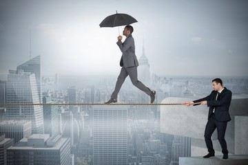 Young business man pulling a tightrope for businessman