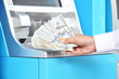 Hand holding money - US dollar banknotes in front of ATM