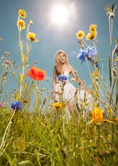 Hübsche blonde Frau vergnügt sich auf einer Blumenwiese