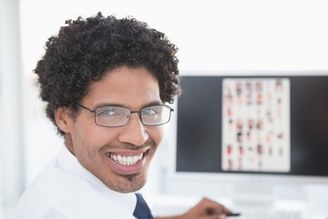 Young editor smiling at camera at his desk
