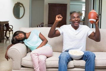 Bored woman sitting next to her boyfriend watching football