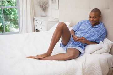 Happy man sitting on bed sending text