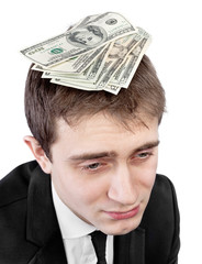 Upset businessman with money on head