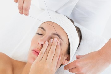 Hands threading beautiful woman's eyebrow
