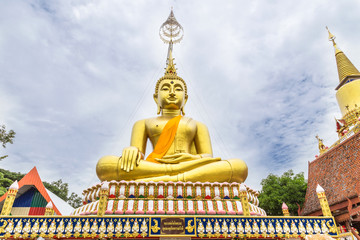 big golden buddha statue sitting at thai temple