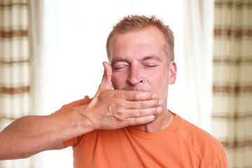 Mann ist müde und hält Hand vor den Mund