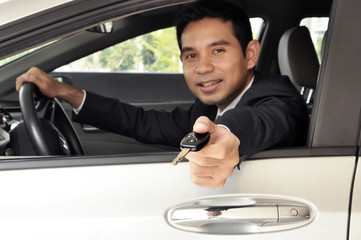 Asian businessman as driver giving a car key