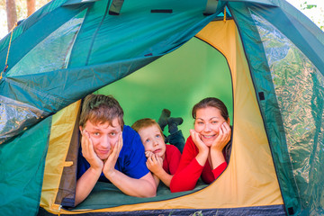Family of three people resting in a tent