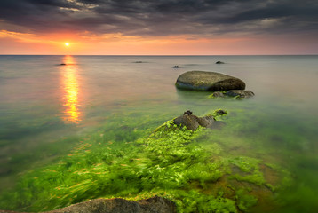 Rocky beach seascape at sunrise with small crabs on the rocks