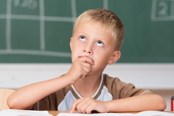 kleiner junge in der schule denkt nach