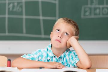 junge in der schule schaut traurig nach oben