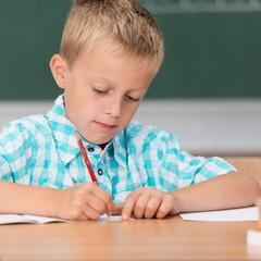 junge in der schule lernt schreiben