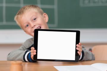 lachender junge in der schule zeigt tablet-pc