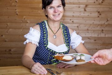 Woman in Bavarian dress gets white sausages served