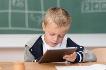 kleiner junge schaut konzentriert auf tablet-pc