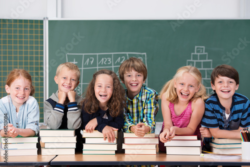 Leinwandbild Motiv lachende kinder stützen sich auf schulbücher