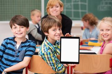 lachende kinder in der schule zeigen tablet