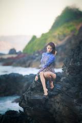 gymnast girl sitting on a stone