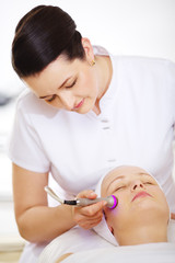 Cosmetician providing lifting procedure with special equipment