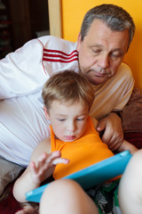 Grandfather and grandson with touch pad