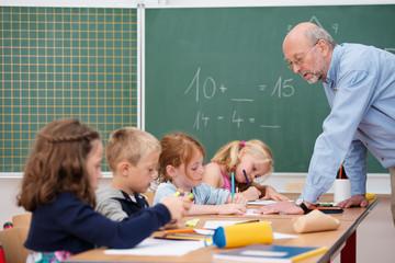 älterer lehrer erklärt den schülern eine aufgabe