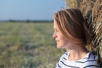 Relaxed woman near hay roll in the field