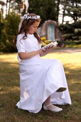 Dziewczynka w białej sukni czyta książeczkę.