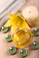 Spa treatment with herbal oil surrounded by spa candles