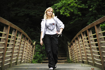 Blond girl walking through a footbridge