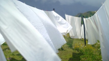 Washed white bed sheets  swaying gracefully in the wind