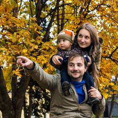 Family in autumn park hand show afar
