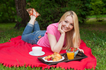 girl outdoor in the park having picnic on the grass