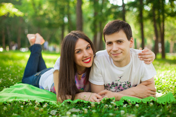 young lovers out in the park lying on the grass