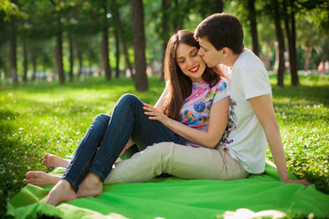 boy kissing girl out in the park sitting on the grass