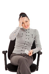 businesswoman sitting in the office chair with headache holding