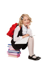 little blonde girl sitting on the books with textbook and red ba