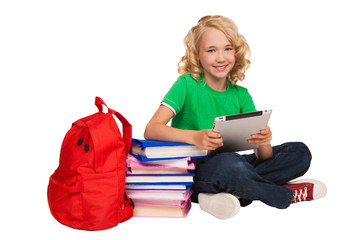 girl sitting on the floor near books and bag holding tablet