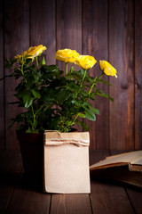 yellow roses and old books on wooden table
