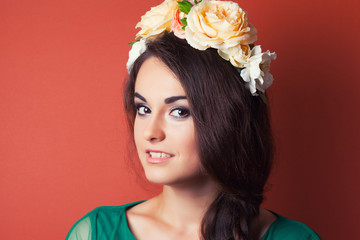 beautiful young woman wearing wreath against red background