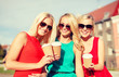 women with takeaway coffee cups in the city