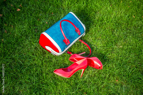 Shoes and women's handbag lay on the grass, women's shoes