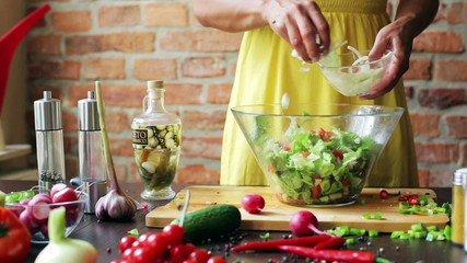 Woman adding onion to the salad in the glass bowl, closeup