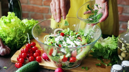 Woman adding chives to the salad in the kitchen, closeup