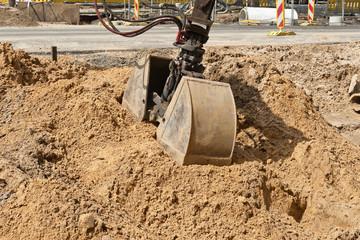 Die Doppelschaufel von einem Bagger greift in einen Sandhaufen