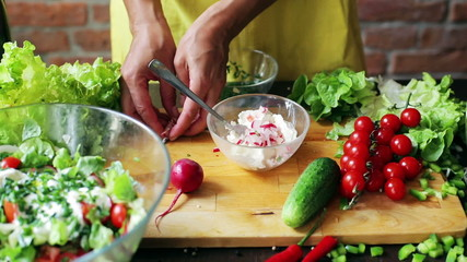 Woman adding radish and chives to the cheese, closeup